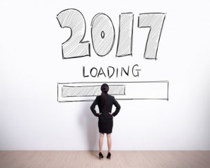 New Year is loading now - Back view of business woman look 2017 text on white wall background